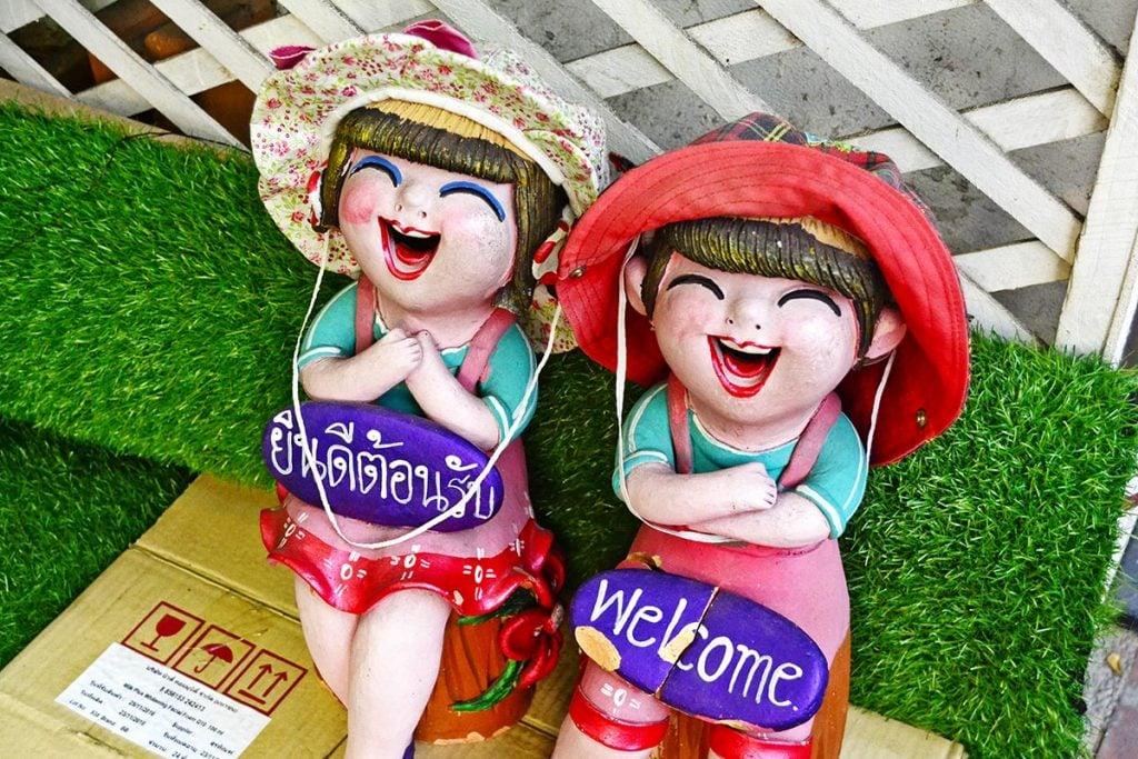 """Two garden figures with """"sawadee krap / sawadee ka"""" signs"""